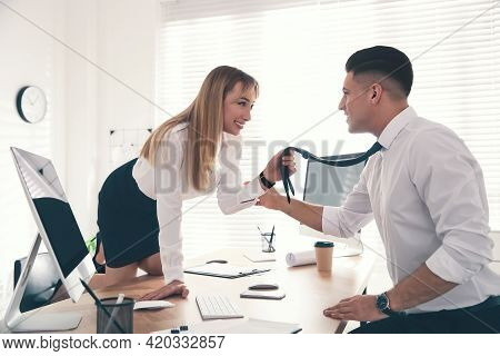 Colleagues Flirting With Each Other During Work In Office. Cheating Concept