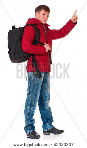 Full length portrait of a young man in winter clothing with backpack showing something isolated on white background