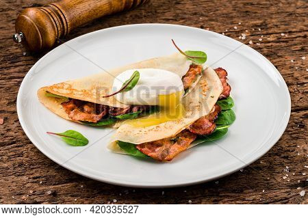 Gourmet Crepes With Poached Egg, Grilled Bacon, Cheese And Herbs For Breakfast