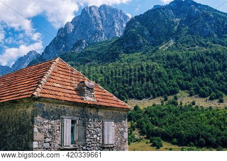 View Of Traditional Albanian Stone House With Orange Slate Roof And Wooden Shutters In Mountain Vill