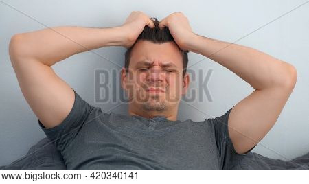 Man With Hangover Waking Up In Bed Feeling Headache Looking At Camera.