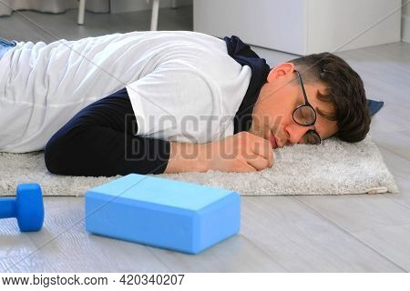 Funny Nerd Man In Glasses Is Falling On Carpet And Sleeping On Floor At Home.