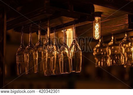 Many Glass Goblets For Wine, Champagne, Martini, Alcoholic Drinks Hang Upside Down Above The Bar. Wa