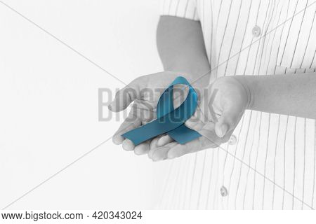 Hand Holding Teal Color Ribbon On White Background With Copy Space. Ovarian Cancer Awareness, Gyneco