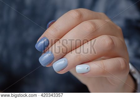 Well-groomed Female Hand On A Dark Background, Manicure With Blue Gel Polish.
