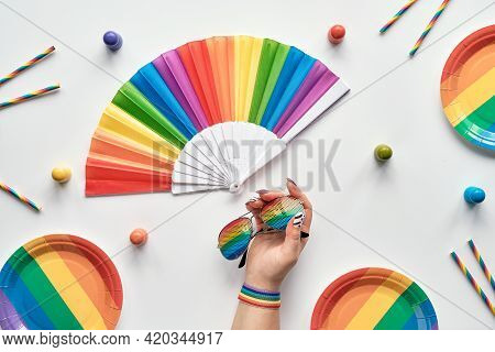 Lgbtq Community Pride Month Rainbow Concept Flat Lay. Hand With Ribbon And Sun Glasses. Rainbow Fan,