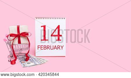 14th Day Of February. A Gift Box In A Shopping Trolley, Dollars And A Calendar With The Date Of 14 F