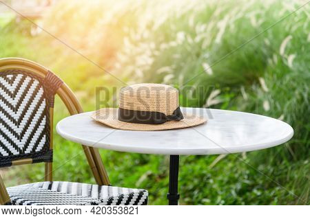 Straw Hat On Table And Chair In Restaurant With Outdoor Garden View.