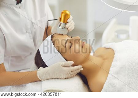 Hands Of Cosmetologist Making Apparatus Phonophoresis Face Procedure For Woman