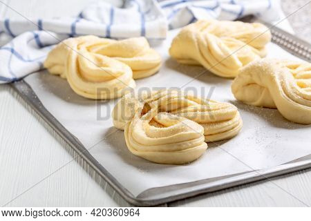 Sweet Wheat Swirling Buns Rise On A Baking Sheet Lined With Parchment. Concept Of Home Baking.