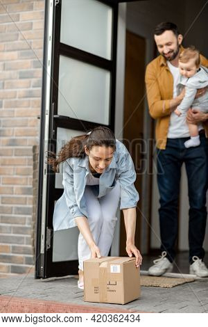 Young Parents With Newborn Kid Customer Order Parcel Delivery Online And Standing In Front Of The Ho