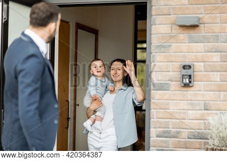 Caucasian Father Waving Goodbye To His Family Before Going To Work. Housewife With Newborn Baby Stay