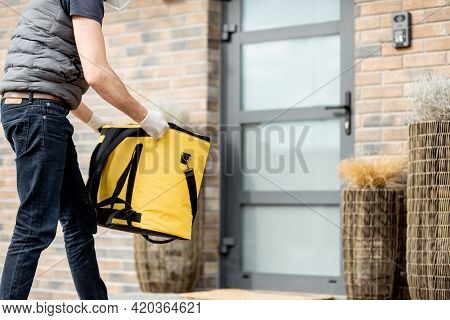 Courier In Green Helmet Wearing Mask And Gloves Holds A Parcel Box And Staying With Yellow Bag Near