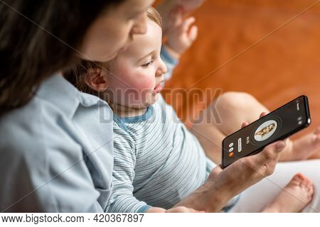 Young Mother With Newborn Kid Making Video Call To A Doctor Using Phone At Home. Concept Of Telemedi