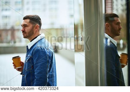 Stylish Guy With A Glass Of Coffee Pondering Life Standing Outside. Photo With Reflection. Lifestyle