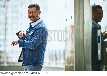 A Stylish Guy Smiles And Points His Finger At The Clock On His Hand Standing In The Street. Photo Wi