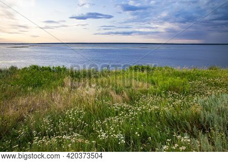 Landscape Of Meadow With Flowers And River. Scenic View Of Beautiful Cloudy Sky Above The River At S