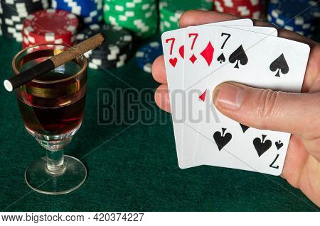 Poker Cards With Three Of A Kind Or Set Combination. Close Up Of Gambler Hand Keeps Playing Cards In