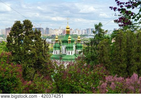 Panoramic View Of The City Of Kiev Or Kyiv. The Gilded Domes Of The Cathedral Among The Blooming Syr
