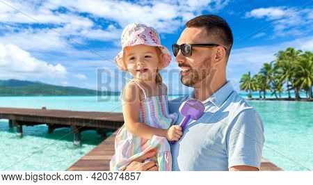 family, fatherhood and travel concept - happy smiling father with little daughter on wooden bridge over tropical beach background in french polynesia