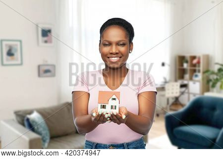mortgage, real estate and accommodation concept - happy smiling african american woman holding house model over home room background