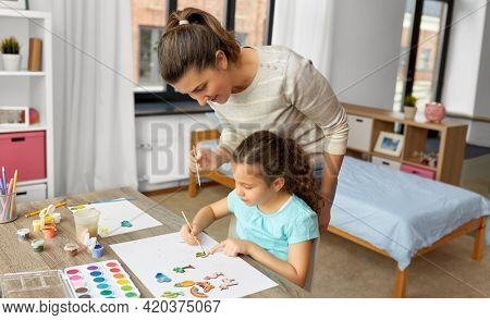family, motherhood and leisure concept - mother spending time with her little daughter drawing or painting wooden chipboard items with colors at home
