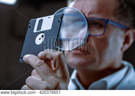 Middle-aged Forensics Expert Examining A Retro Floppy Disc With A Magnifying Glass During An Investi