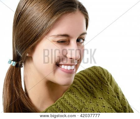 portrait of attractive teenager girl smiling in cheerful mood gives a wink, over white