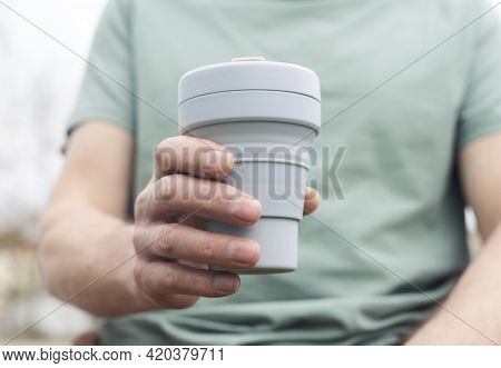 Collapsible Cup For Takeaway Coffee Or Tea. Male Hand With Sustainable Silicon Mug
