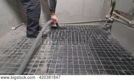 A Worker Is Cleaning Dust With A Vacuum Cleaner On The Floor. Cleaning Service. Dust Removal With Va