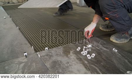 Adhesive Solution For Gluing Ceramic Floor Tiles. Professional Worker Gluing Decorative Tiles To The
