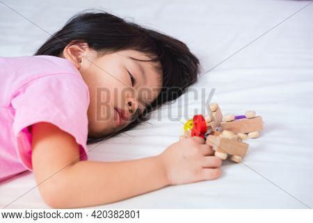 Sleepy Kid On White Bed, Playing Number Wooden Toy. Asian Child Lying Down On Mattress. Dry Skin Und