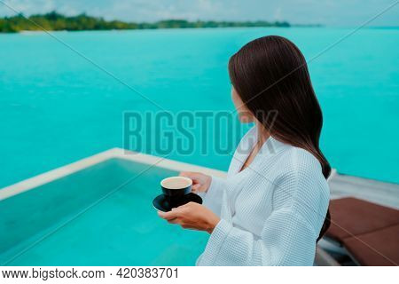 Woman having breakfast at luxury hotel room drinking coffee cup with view of turquoise ocean and overwater infinity swimming pool. Paradise getaway in the Maldives island.