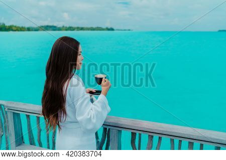 Luxury hotel travel vacation. Woman drinking breakfast coffee relaxing at ocean view from overwater bungalow balcony wearing bathrobe. Resort lifestyle Asian guest enjoying room service.