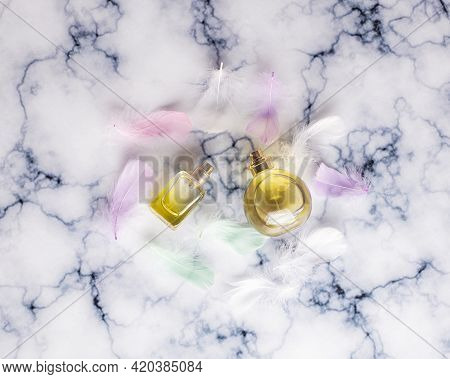 Perfume With A Delicate Scent. Perfume Bottle Surrounded By Colorful Feathers