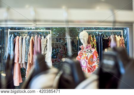 A Mannequin In A Summer Shirt Near A Hanger With Colorful Summer Clothes