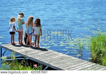 Little Girls Standing At The End Of A Dock