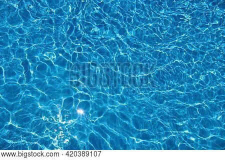 Abstract Summer Background With Clear Blue Water In The Swimming Pool And Sun Reflection. Ripple Wat