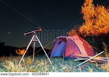 Reflector Telescope On A Tripod Tourist Camping Tent At Night Under Starry Sky. Country Trip For Obs