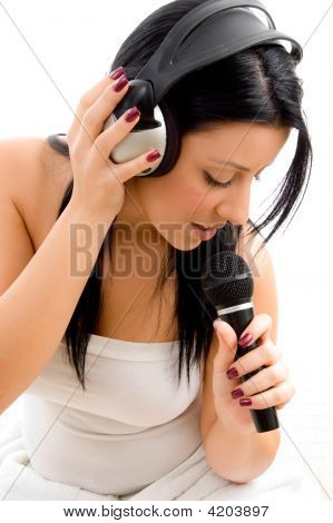 Top View Of Female Holding Headphone And Microphone Against White Background