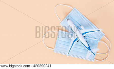 Airplane And Medical Masks On Neutral Beige Background With Copy Space. Minimal Concept Of Travel An