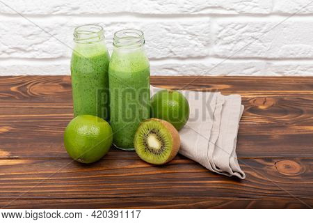 Jars Of Healthy Green Smoothie With Fresh Spinach. Fresh Green Smoothie On Rustic Wooden Background.