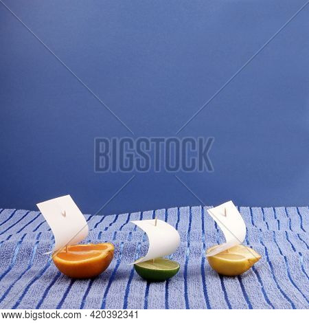Three citrus fruits sail boats on blue towel waves abstract concept photo of wide sea or ocean on blue copy space background. Abstract healthy food lemon, lime and orange