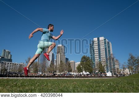 Full Length Of Healthy Man Running And Sprinting Outdoors Near City Skyline. Male Urban Runner. Dyna