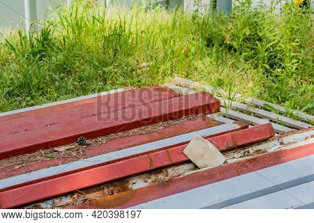 Metal Construction Beams Laying On Ground In Tall Grass.