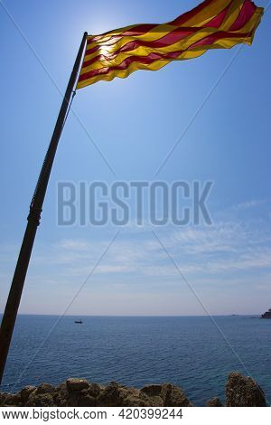 Calella De Palafrugell, Spain, May 1, 2020 - Catalan Flag On Flagpole Over Sea In Backlight Copy Spa