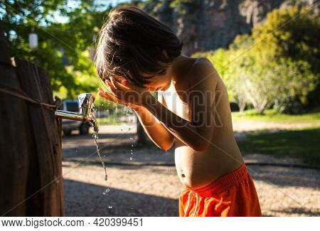 Tired Of The Heat, The Child Washes His Face With Water From A Tap In The Courtyard Of The House. Th