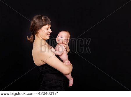 Portrait Of Mother And Her Newborn Baby Together. Happy Mommy Kissing Baby Boy. Mother Kissing Her A