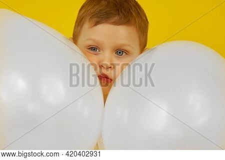 The Sad Face Of A Blue-eyed Boy Between The Balls On A Yellow Background. The Emotion Of Sadness And