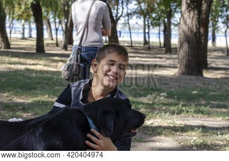 Emotional Portrait Of A Boy Stroking A Black Dog With A Blue Collar In The Park. A 10-year-old Child